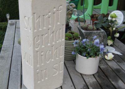 Vrij werk in witte steen, staat bij grafsteen